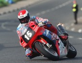 PACEMAKER, BELFAST: With flames flying from his exhaust James Courtney blasts through Church Corner at the 1998 North West 200 on his 750cc Honda.